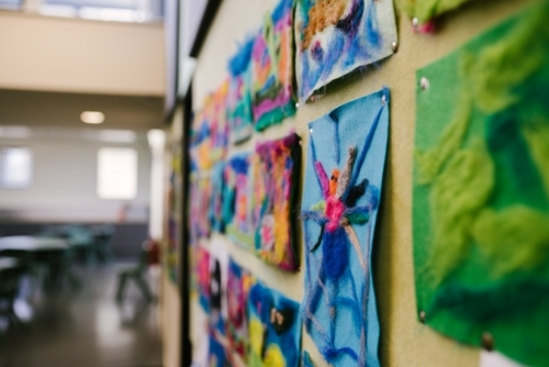 Colourful student artwork on pinboard