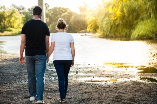 Couple holding hands walking away along river