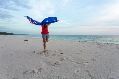 Australia Day - a woman leaps into the air with the Australian Flag above her head on a beach