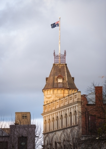 Australian flag flying above a heritage building