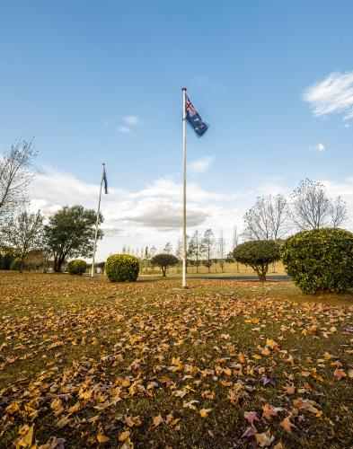 Australian flag moving in breeze with autumn eaves under flag pole
