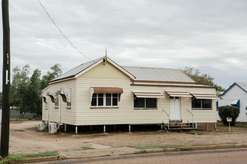Australian Queenslander cream coloured house with brown trimming