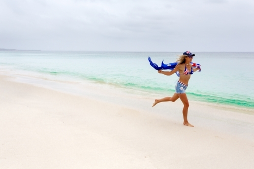 Australian woman running along the beach. She has the Australian flag printed on her cossie