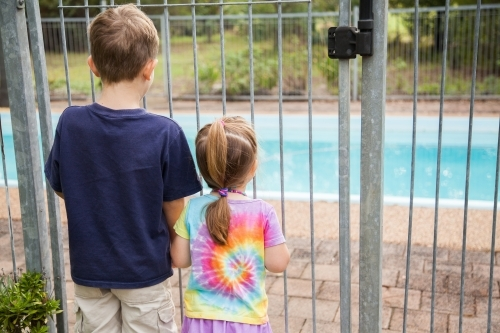 Two young kids looking through pool fence bars