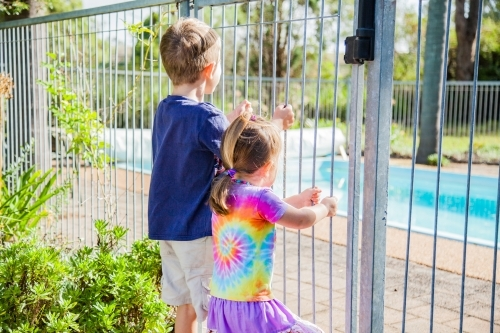 Children holding fence bars looking into pool yard
