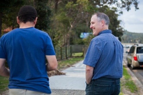 Two men talking to one another as they walk down footpath