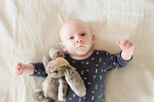Baby boy looking at camera with soft toy rabbit
