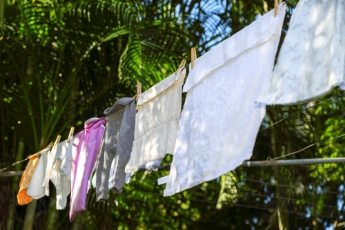 Baby clothes drying on clothes line.