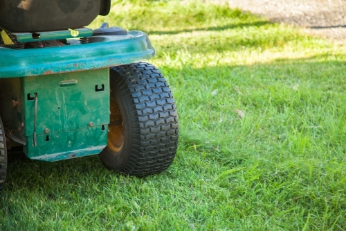 Back of a green ride on lawn mower cutting the grass