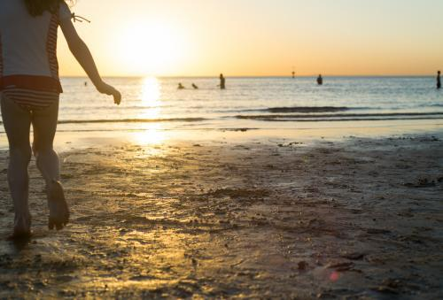 Back view of a young girl at the beach running towards the ocean at sunset