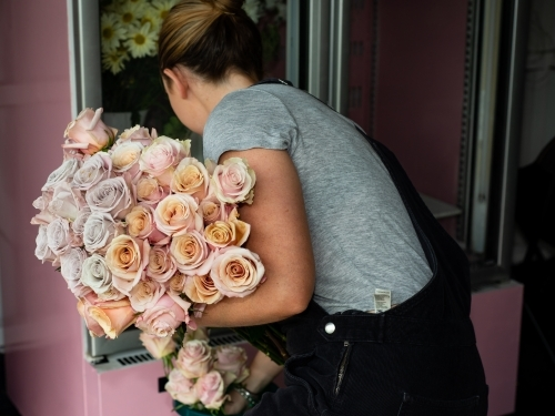 Back view of female florist with a large bunch of beautiful pastel coloured roses