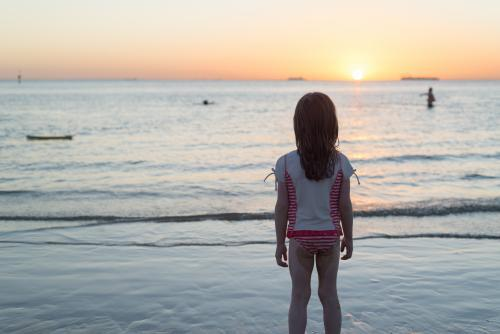 Back view of a lone young girl standing on the beach watching the sunset