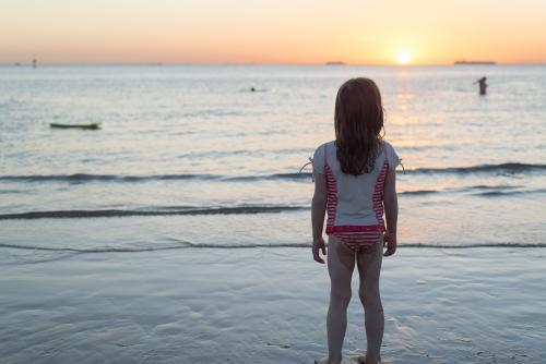 Back view of a lone young girl standing on the beach watching the sunset over the ocean