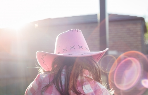 Back view of a young girl dressed in a pink cowgirl hat with sunflare
