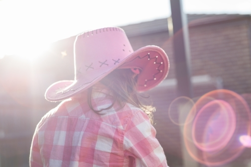 Back view of a young girl dressed as a cowgirl with sunflare