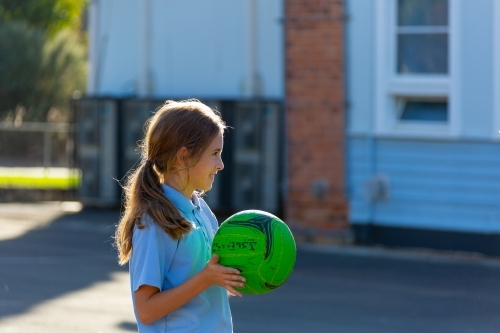 backlit child holding green netball at school