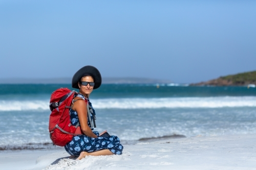 Backpacker with rucksack sitting on white sand beach
