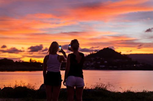 Backpackers photographing a brilliant sunset on their phones.