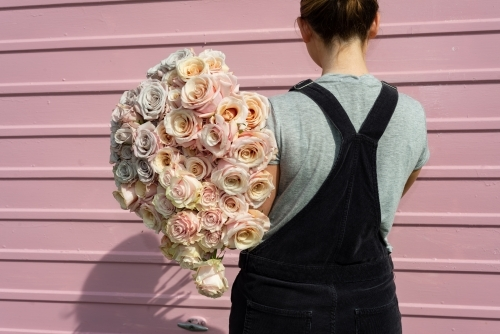 Backview of woman holding a large bunch of beautiful pastel coloured roses with a pink background