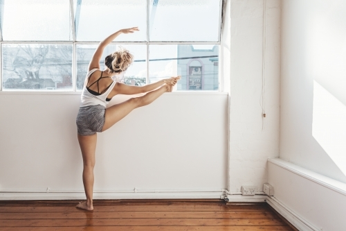 Ballet dancer practicing poses in a bright white studio