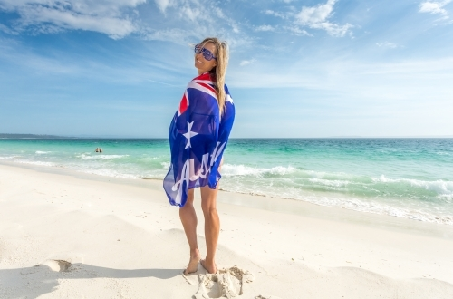 Barefoot woman on the beach with Australian flag wrapped around her