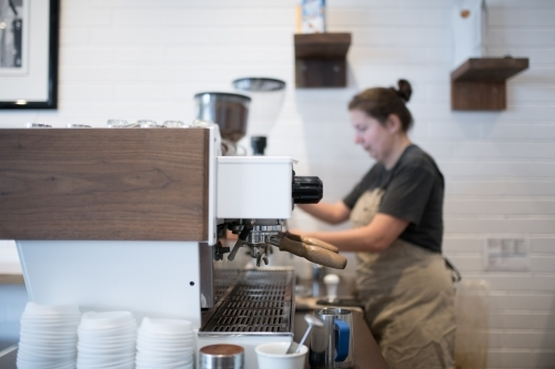 Barista grinding coffee beans into group head