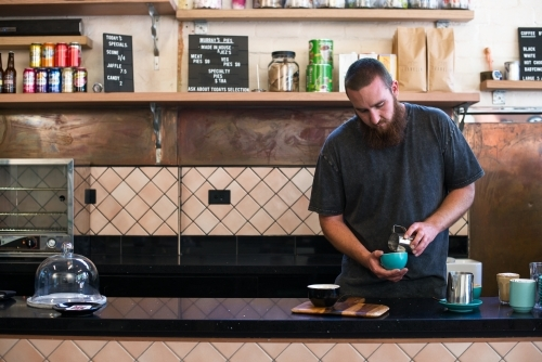 Barista making coffee inside cafe shop