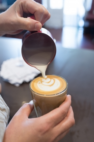 Barista pouring milk into coffee cup