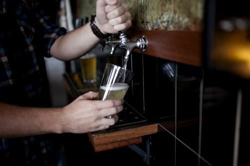 Bartender pouring drink on tap at local craft beer bar