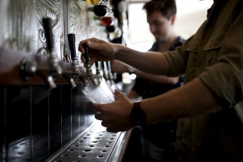 Bartenders pouring drinks on tap at local craft beer bar