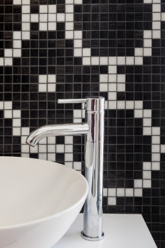 bathroom sink with chrome tap and black and white mosaic tiles