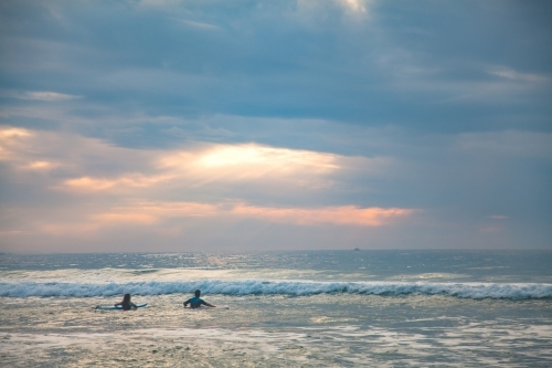 Two surfers making their way out to the breakers in early morning