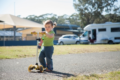 Little girl riding on a scooter in caravan park