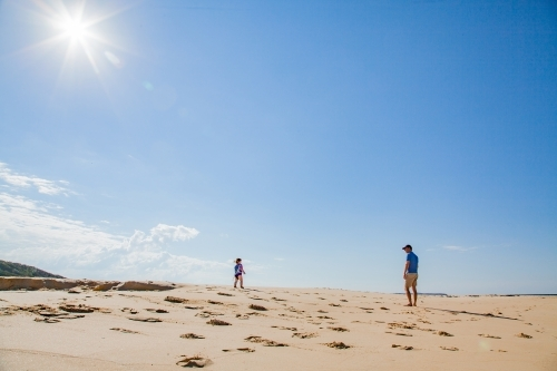 Father and young daughter walking along sunlit beach together