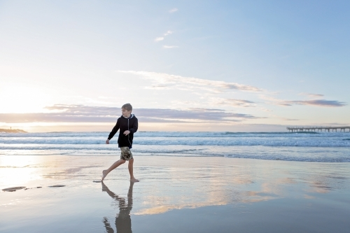 Beach reflections with boy running on wet sand