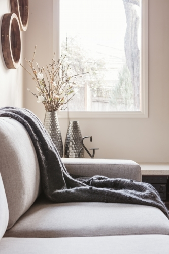 Beautiful inviting sofa with throw rug and soft window light behind