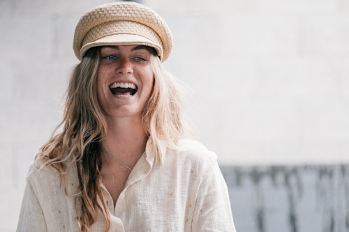 Beautiful laugh from a young woman wearing a cap.