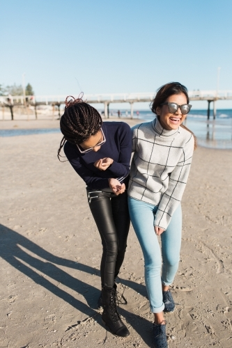 Best friends spending time on the beach laughing