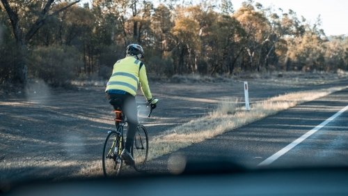 Bike rider alongside country highway