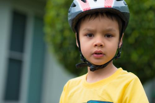 Cute mixed race boy wearing a helmet and riding his bike