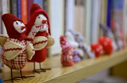 Bird dolls as Christmas decorations on a bookshelf