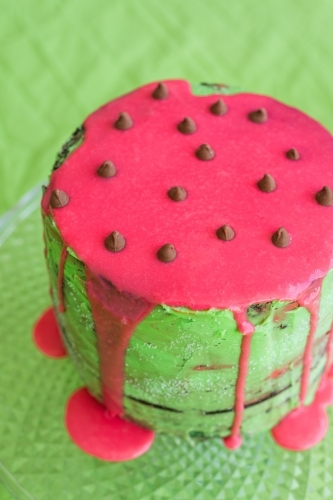 Birthday cake in watermelon theme, green icing with hot pink dripping ganache down side of cake
