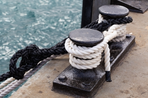Black and white ropes tied off at a wharf
