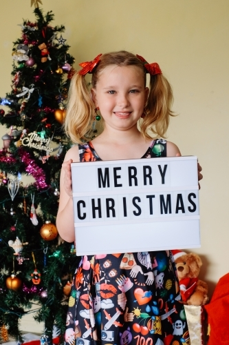 Blonde girl holding a Merry Christmas sign