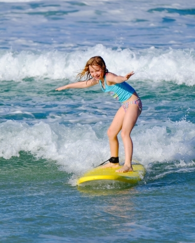 Blonde girl surfing off South Stradbroke Island on the Gold Coast