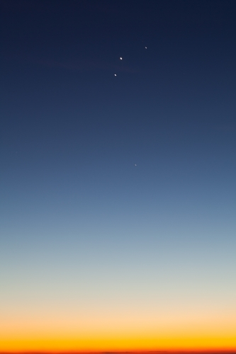 Blue and yellow dawn sky with planets aligned