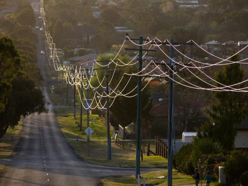 Sunlight on power lines looping off into the distance in a town