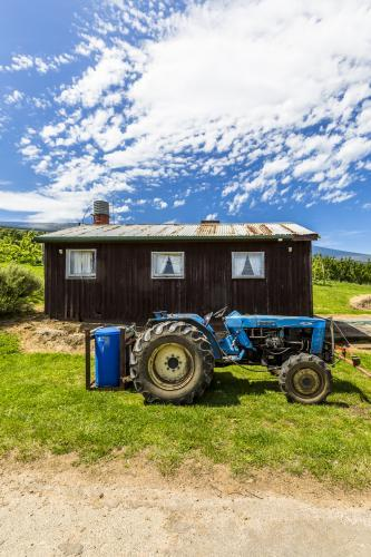 Blue tractor in front of small building