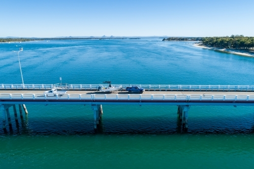 Blue ute towing a fishing boat on bridge over water.