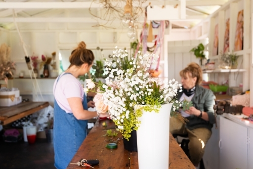 Blurred female florist and assistant at work bench with vase of baby's breath flowers in foreground